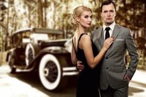 Retro couple against old car.